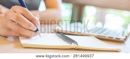 Woman Hand Is Writing On Notepad With Pen In Office.