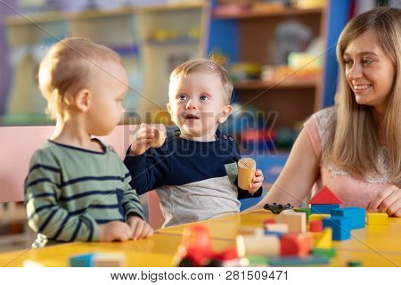 Nursery Babies Kids Playing With Teacher In Kindergarten
