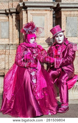 VENICE, ITALY - FEBRUARY 18, 2017: Unidentified participants wear traditional colorful costumes and white masks during famous Carnival taking place each year on february in Venice, Italy.