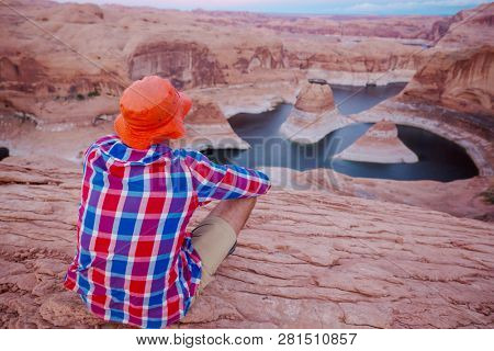 Unusual natural background. Reflection Canyon on Lake Powell, Utah, USA. Inspiring hiking scene-man resting on the beautiful sunset point.