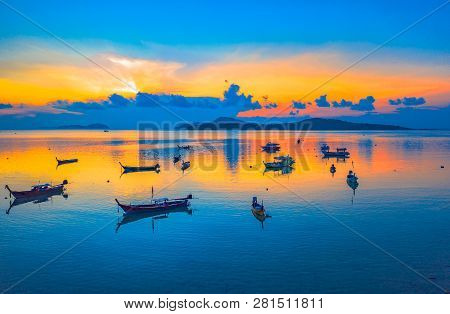 Sweet Sunrise Above Fishing Boats On The Beach. Morning Light Shines Up From The Edge Of The Sea. A