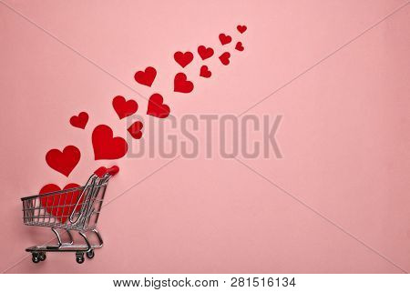 Shopping trolley and decorative red hearts on pink background with copy space. Valentine's day, Mother's day,  wedding
