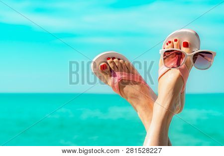 Upside Woman Feet And Red Pedicure Wearing Pink Sandals, Sunglasses At Seaside. Funny And Happy Fash