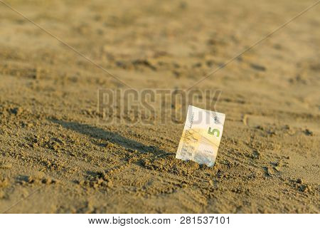 Banknote Of Value Of Five Euro In The The Sand On The Beach. Concept Of Cheap Travel And Vacation. P