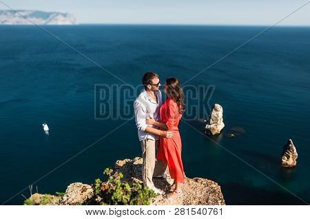 Couple In Love At Sunset By The Sea. Honeymoon. Honeymoon Trip. Boy And Girl At The Sea. Man And Wom