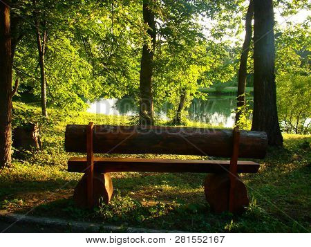 A Sunlit Wooden Bench On The Waterside