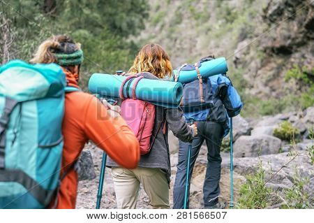 Group Of People With Backpacks Doing Trekking Excursion On Mountain - Young  Tourists Walking And Ex