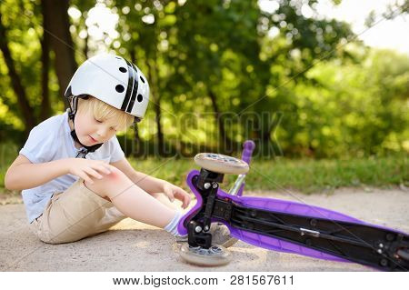 Toddler Boy In Safety Helmet Learning To Ride Scooter. Little Child Crashing During Active Outdoors