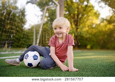 Little Boy Having Fun Playing A Soccer/football Game On Summer Day. Active Outdoors Game/sport For C