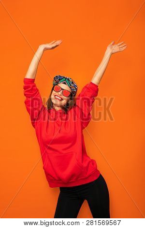 Young Girl In Red Hoodie On Orange Background