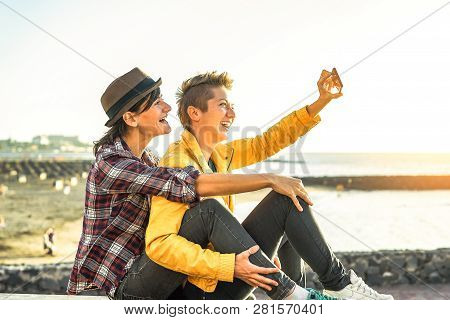 Happy Gay Couple Taking A Selfie With Mobile Smart Phone Camera On The Beach At Sunset - Lesbians Ha