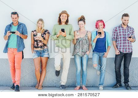 Young People Watching On Their Smart Mobile Phones Leaning On A Wall - Generation Addicted To New Te