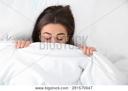 Young woman sleeping under blanket, top view. Bedtime poster