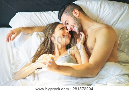 Young Loving Couple Lying In Bed Cuddling Looks Each Other Under White Blankets - Beautiful And Happ