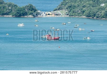 Bombinhas - Sc, Brazil - December 18, 2018: Touristic Red Ship Sailing In Front Of The Praia Da Sepu