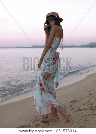 Slim Young Model Posing On The Beach For The Summer Collection Dresses. Demonstrate Light White Dres