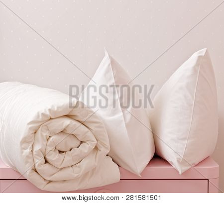A rolled up blanket and two pillows lie on the dresser. Household poster