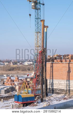 Crawler Cranes, Piles, Concrete Slabs And Cranes On The Construction Site Near The Multi-storey Buil