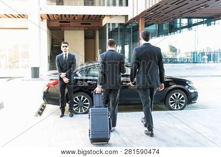 Rear View Of Bodyguard Escorting Vip While Leaving From Office Premises