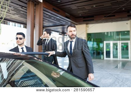Alert Bodyguards And Boss Looking Around While Reaching Towards Car Outside Office Building