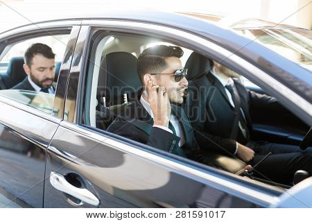 Young Bodyguard Listening To Earpiece While Sitting In Car With Vip