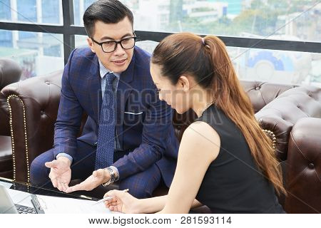 Mature Vietnamese Entrepreneur Talking To His Assistant In Cafe