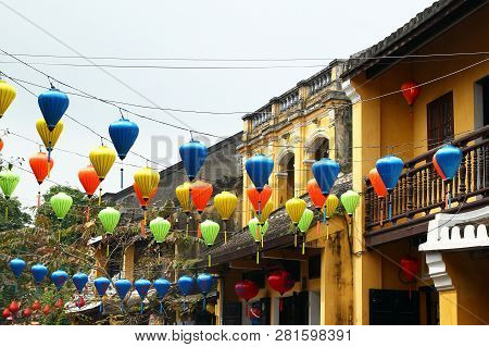 Hoi An, Vietnam - February 12, 2018: View On A Street In Old Town With Yellow Buildings, Trees And C