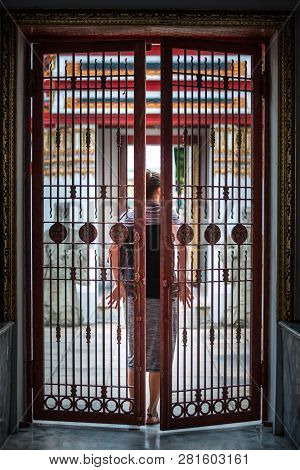 Woman Closes The Iron Gate Door Behind Her