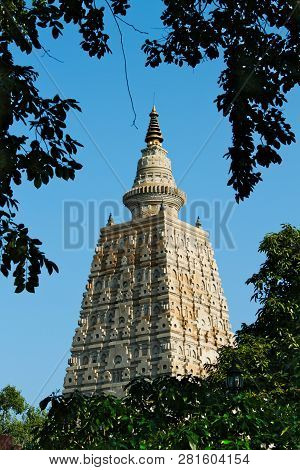 Famous Mahabodhi Temple In Bodhgaya In India. Around Branches Of A Tree With Green Leaves.