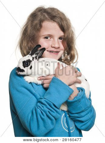 Girl holding Dalmatian rabbit, Oryctolagus cuniculus, 4 months old, in front of white background