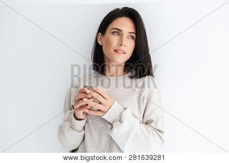 Photo of gorgeous woman 30s holding cup with tea while standing over white wall indoor poster