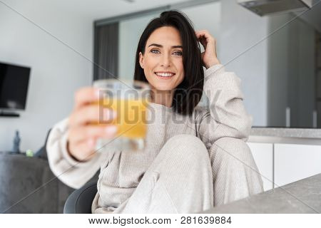 Image of attractive woman 30s drinking orange juice while resting in bright modern room poster