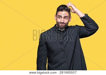Young Christian priest over isolated background confuse and wonder about question. Uncertain with doubt, thinking with hand on head. Pensive concept.