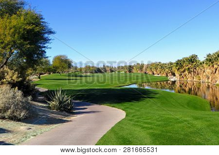 A Beautiful View Of A Par 5 With The  Desert Surrounding The Hole As Well As A Pond.  The Golf Cours