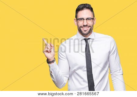 Young handsome business man wearing glasses over isolated background with a big smile on face, pointing with hand and finger to the side looking at the camera.