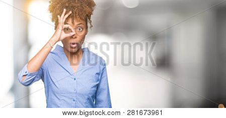 Beautiful young african american business woman over isolated background doing ok gesture shocked with surprised face, eye looking through fingers. Unbelieving expression.