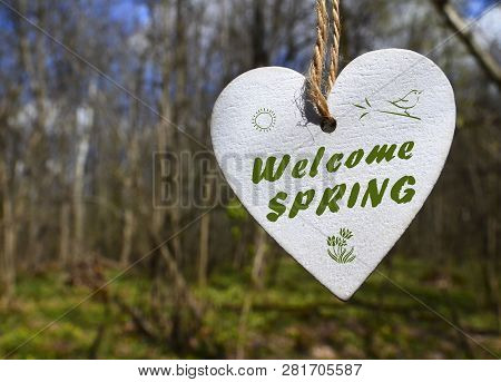 Welcome Spring Greeting Card With Decorative White Wooden Heart With Text On A Blurred Spring Forest