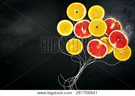 Food Art. Fruit Slices On A Dark Chalkboard Background With Strings. Balloons From Fruit Slices. Hea