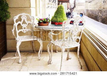 White Vintage Wrought Iron Gardening Furniture, Set Of Empty Round Table And Two Elegant Chairs On B