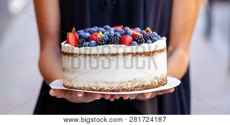 The Girl Is Holding A Cake With Forest Berries, Strawberries, Blueberries, On The Street In The City