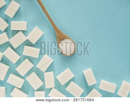 Background Of Sugar Cubes And Sugar In Spoon. White Sugar On Blue Background. Sugar With Copy Space.