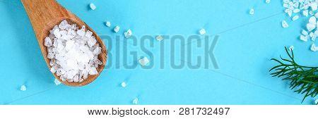 Crystals Of Large Sea Salt In A Wooden Spoon And Dill On A Blue Table. Background For Advertising Sa