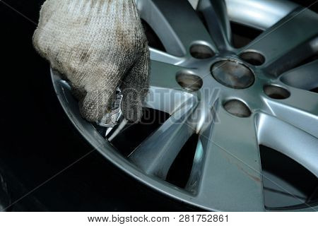 The Hand Of Repair Man And Dirty White Glove Refueling Air Into The Tyre Of The Metallic Iron Wheel