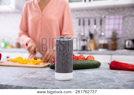 Close-up Of A Woman Working In Kitchen With Smart Speaker In Foreground