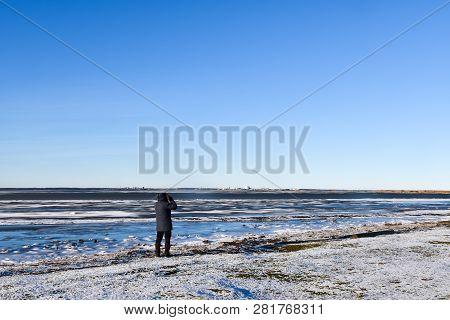 Birdwatcher By An Icy Coast In Winter Season At The Swedish Island Oland