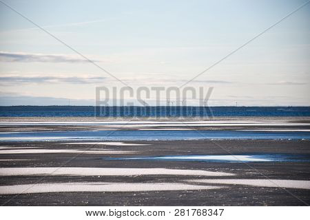 Ice Covered Water Pattern With Windmills In The Horizon By The Coast Of The Baltic Sea At The Swedis