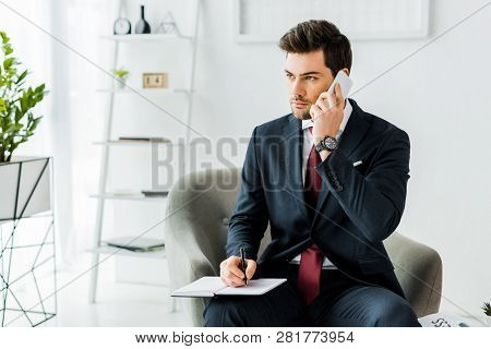 handsome businessman in formal wear sitting on armchair and witting in notebook while talking on smartphone in office poster
