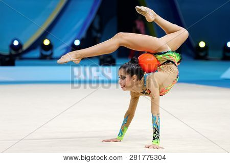 KIEV, UKRAINE - AUGUST 28, 2013:  Unidentified female athlete performs with ball during 32nd Rhythmic Gymnastics World Championships. The event is held in Palace of Sport