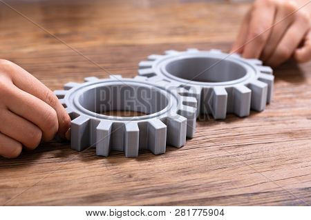 Businessperson Joining Gears On Desk