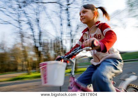 motion blur of a little girl biking poster